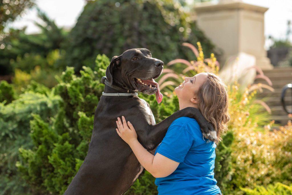 Large Black dog standing on back legs hugging a Charlotte dog trainer.