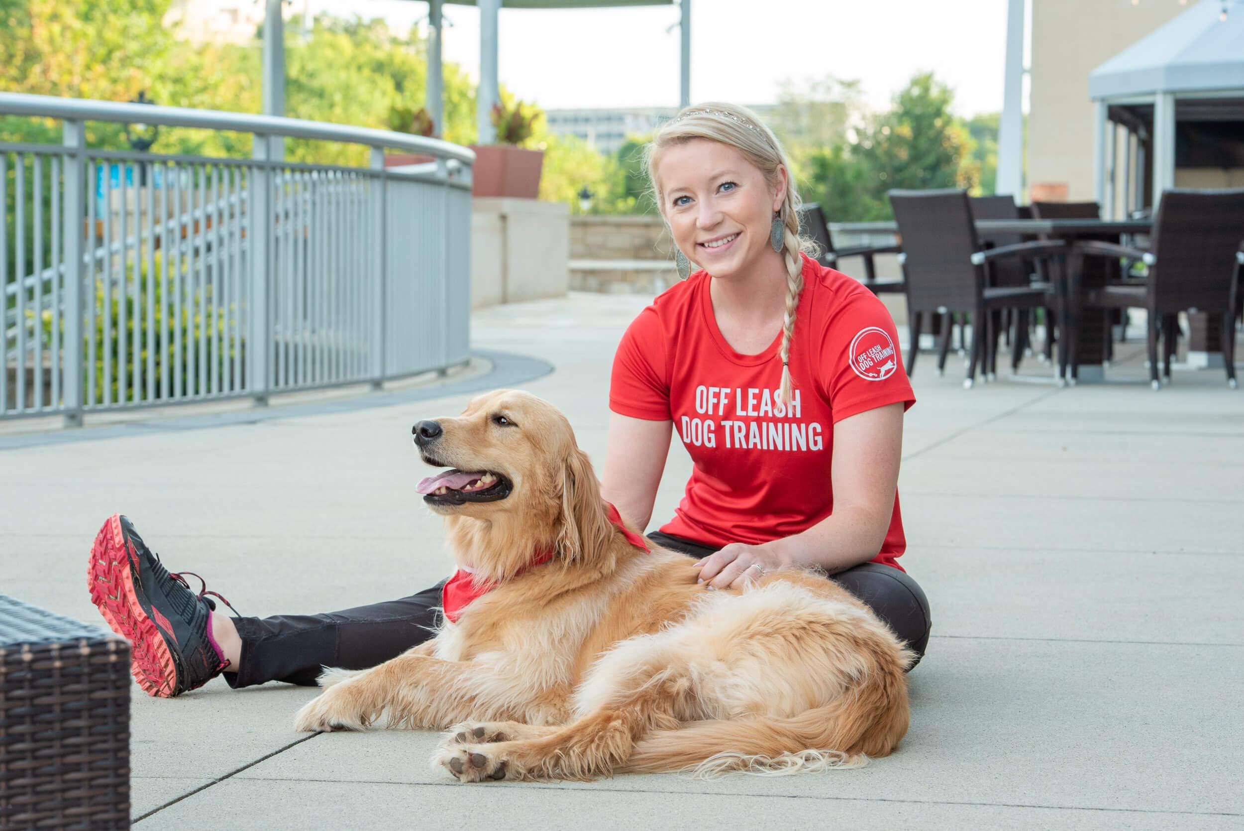 Charlotte dog trainer sitting next to golden retriever.